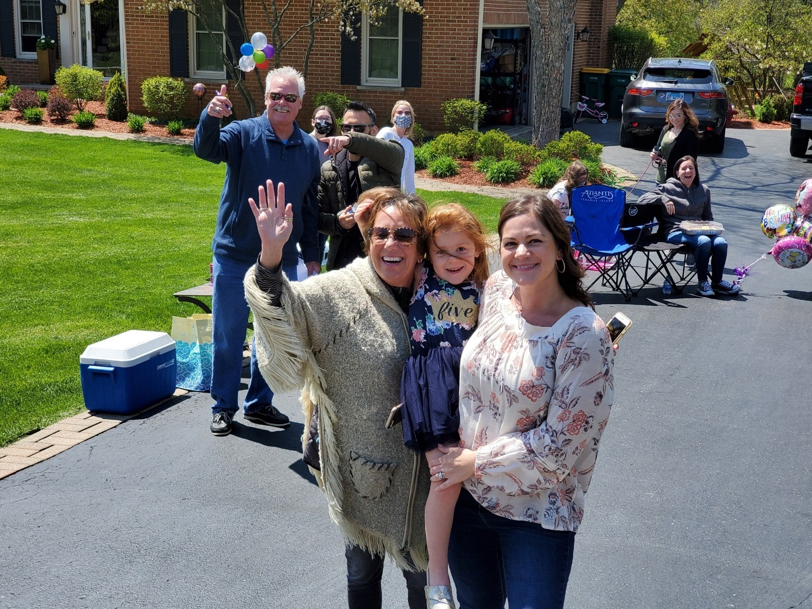The Krumwiede family waves as people drive by for Peyton's birthday